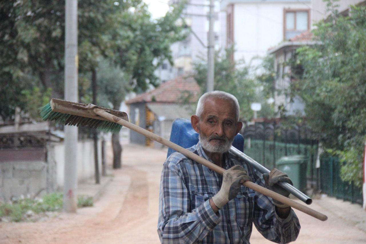 İhtiyar delikanlı elinde süpürge ve küreği ile mahallesinde çöp bırakmıyor
